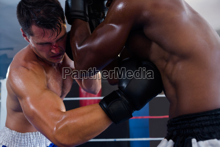 male boxer punching competitor in ribs