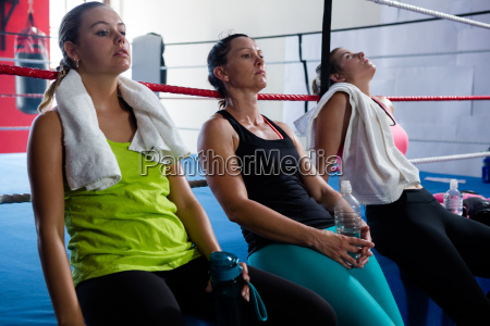 tired female boxers leaning on rope