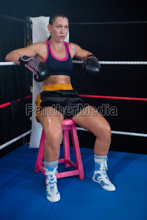 young female boxer sitting on stool