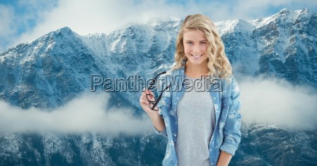 mujer sonriente sosteniendo anteojos contra montanyas