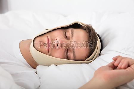 man sleeping with anti snoring bandage