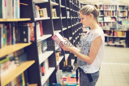 mujer joven que elige un libro