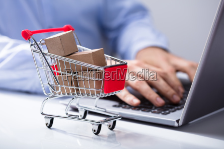 man using laptop with shopping cart