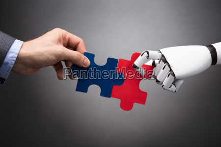 businessperson y robot holding jigsaw puzzle