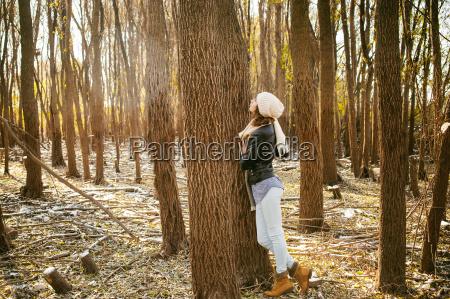 young woman walks among the trees