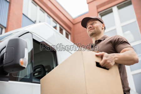 joven entrega hombre llevando caja de