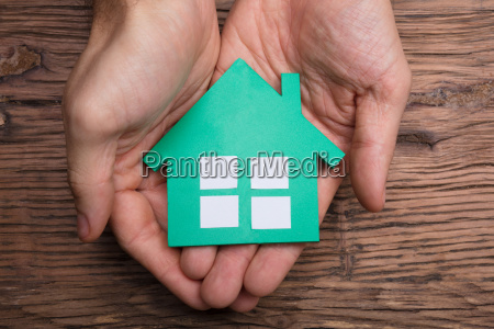 hands holding paper house