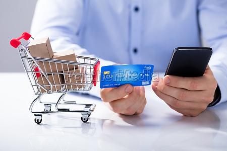 hombre usa tarjeta de credito para