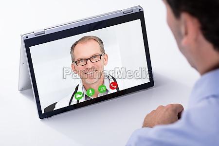 man video conferencing con su doctor