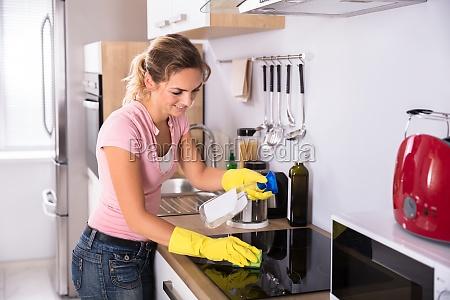 mujer limpieza sucia estufa de induccion