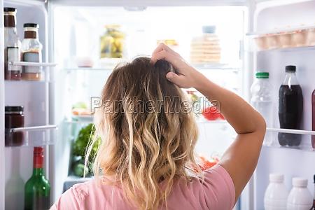 mujer confundida mirando en el refrigerador