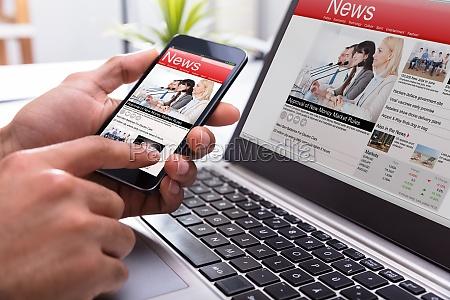 businessperson holding smartphone con noticias en