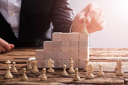 businessperson organizando pieza de ajedrez sobre