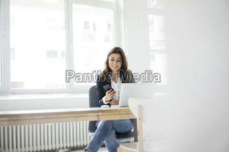 businesswoman sidder ved skrivebordet pa kontoret