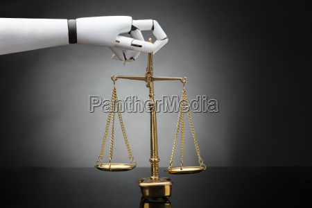 robots hand holding justice scale