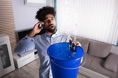 man calling plumber while leakage water