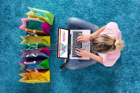 woman sitting on carpet and shopping