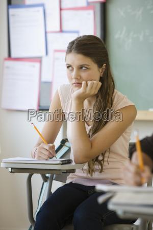 girl writing in classroom