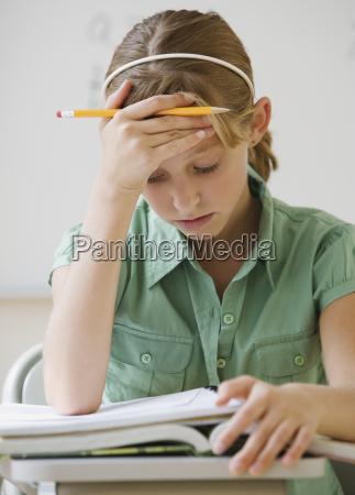 teenaged girl reading at school desk