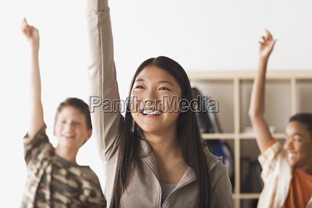 school children rising hands in classroom