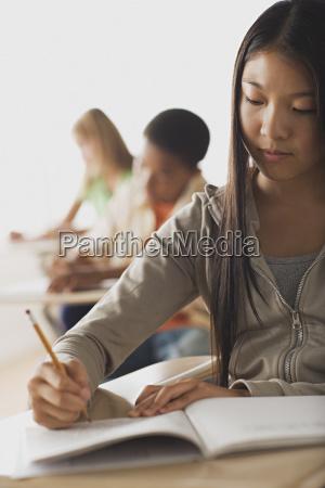 school kid writing in their copybooks
