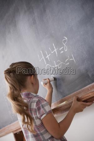 schoolboy writing on blackboard