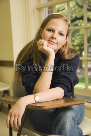teenage girl sitting at school desk