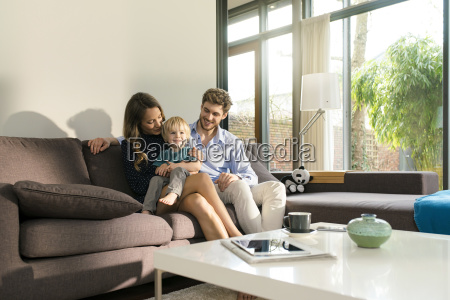 smiling parents and son sitting on