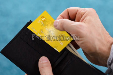 person removing credit card from wallet