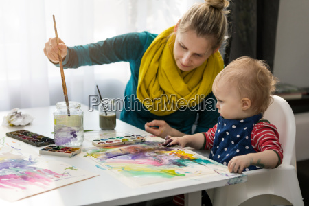 mother teaching child how to paint