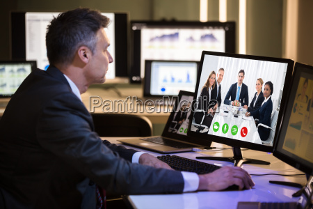 businessman video conferencing with happy colleagues