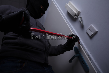 ladron tratando de romper la puerta