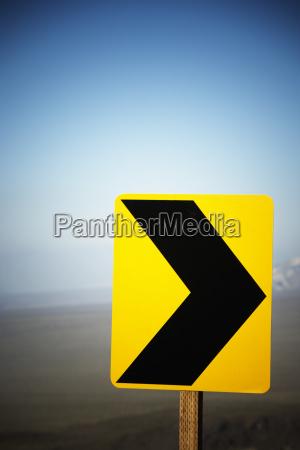 una flecha amarilla de precaucion a
