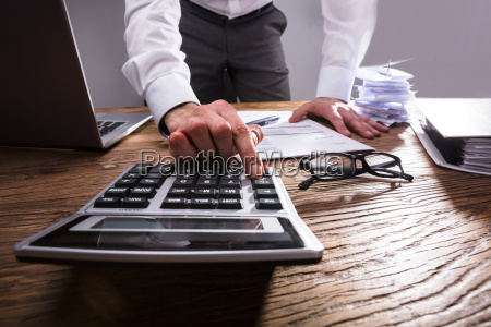 businessperson calculating bill with calculator