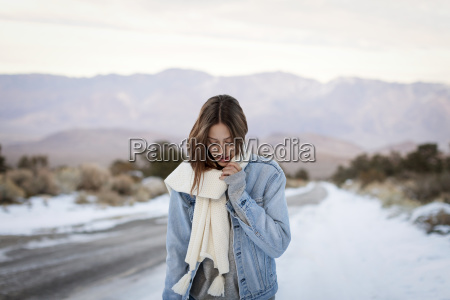 young woman holding muffler while standing