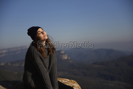 woman with eyes closed sitting on