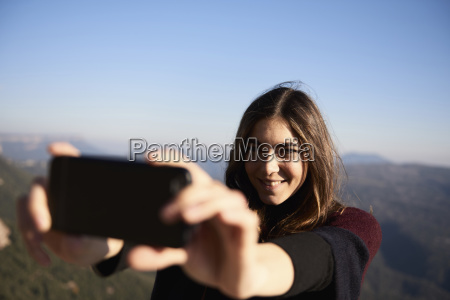 woman taking selfie while standing against