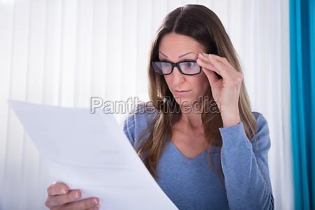 mujer con anteojos mirando el documento