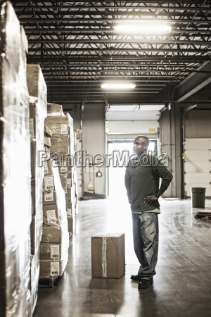 african american male warehouse worker checking