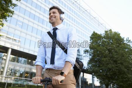 empresario usando auriculares viajando para trabajar