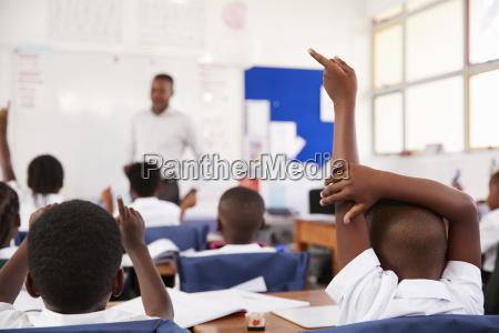 kids raising hands to answer teacher