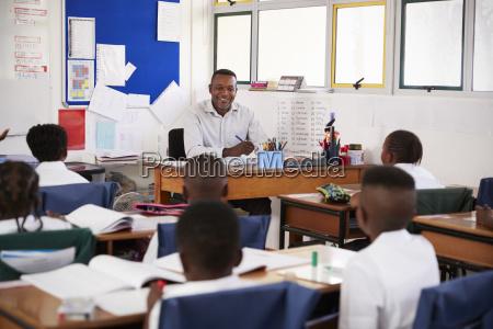teacher and kids sitting at desks
