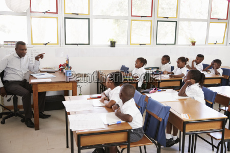 teacher teaching kids from his desk