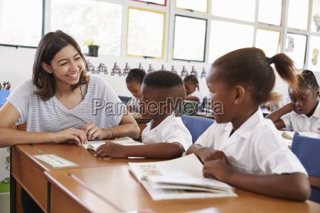 volunteer teacher helping school kids in