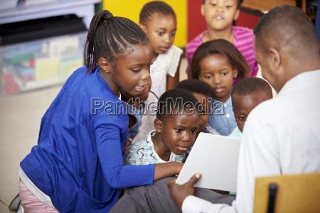 teacher showing kids a book during