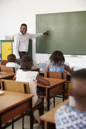 teacher at chalkboard in elementary school