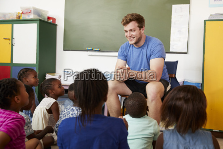 elementary school kids sitting on floor