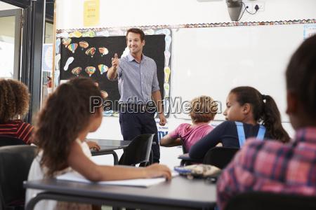 teacher gesturing to class in an