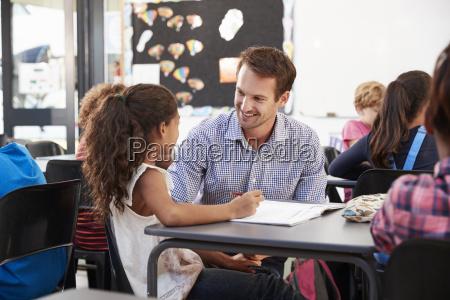 teacher and schoolgirl at her desk