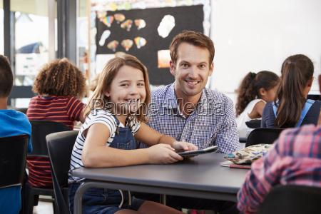 maestro y colegiala usando tableta en